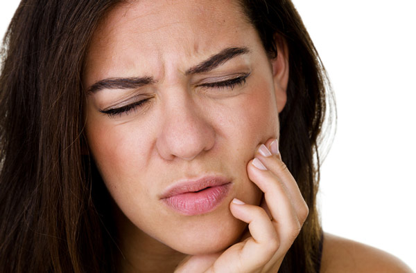 Woman holding jaw due to TMJ pain